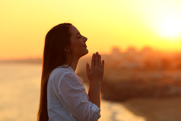 Profile of a woman praying at sunset