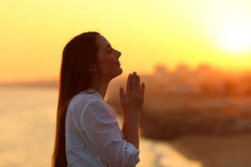 Profile of a woman praying at sunset