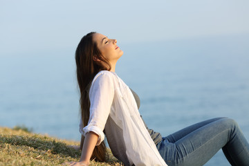 Relaxed woman breathing fresh air sitting on the grass