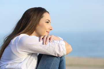 Relaxed woman thinking looking away on the beach