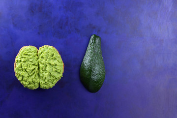 Avocado and sandwiches with a spread of avocado on an ultraviolet background, a green spread with...