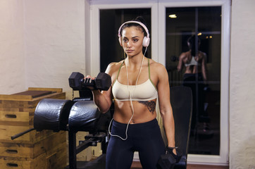 Focused female bodybuilder / fitness woman lifting dumbbells  in gym