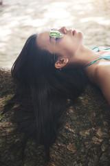 relaxation girl in a sunglasses blue bikini lies on the tree near the sea