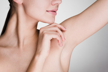 woman after the shower takes care of the underarm skin on a gray background