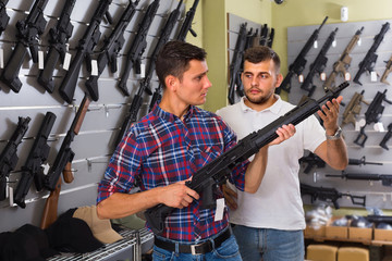 Two guys are choosing pneumatic rifle