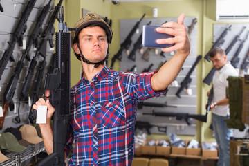 Adult man is taking selfie on phone with air gun