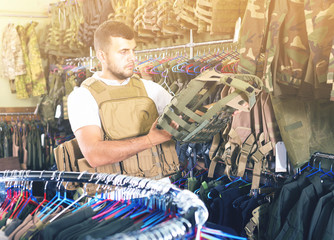 man with flak jacket in hands in airsoft market