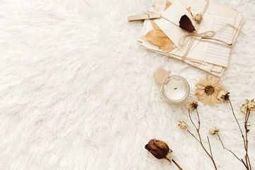 Candles, old letters and dried flowers at white background. Cozy vintage. Flat lay, top view