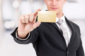 Businessman holding a blank gold business card in his hand