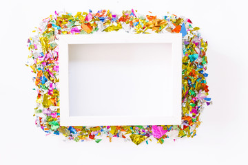 White photo frame with colorful paper on white background.flat lay, top view