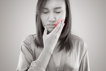 Suffering from toothache. Beautiful young woman suffering from toothache while standing against grey background