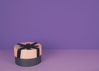 Pink gift box against ultra violet and lilac background.