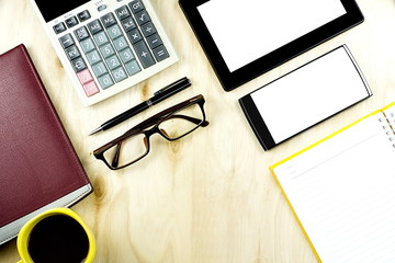 Brown eyeglasses blank screen smartphones and tablet PC on the wooden desktop with financial calculator in composition