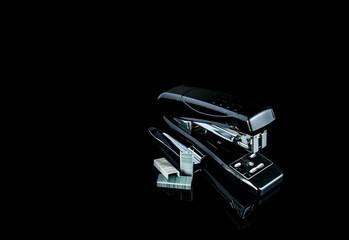 Black stapler and staples on dark background.