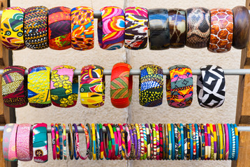 Colorful Bangle Bracelets made with bright fabrics and leather. The bracelets are on display and for sale.