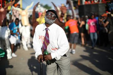 A reveller dances as he parades along a street at the Carnival of Jacmel