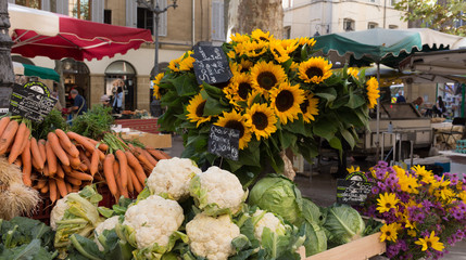 Sunflowers and Vegetables at an outdoor farmers' market in Aix en Provence, France. Cauliflower, carrots, cabbage and sunflowers are for sale.