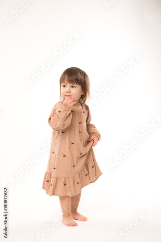 a2dadbf5b Cute little girl in beige dress isolated on white background ...