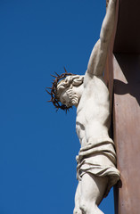 A statue of the crucifixion with Christ on a cross. Photographed against a deep blue sky in Avignon France.