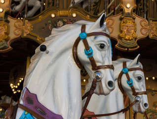 Two White Carousel Ponies with brown bridles on a merry go round in Avignon, France. The golden carousel in in the background.