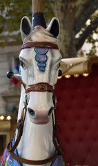 White Carousel Horse on a Merry Go Round in Avignon. The white horse has a brown and lavender bridle.