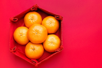 Group of orange tangerine in Chinese pattern tray on red table top. Chinese new year concept.