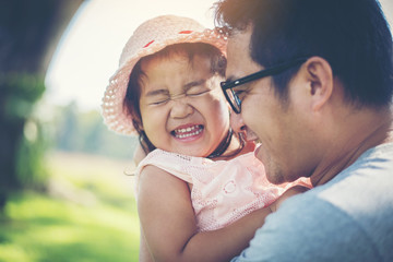 Little girl hugging neck of her daddy, Father playing with daughter happy family time.