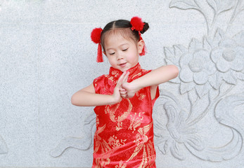 Happy little Asian child girl wearing red cheongsam with greeting gesture celebration for Chinese New Year at chinese temple in Thailand.