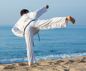 Guy practising karate at seaside