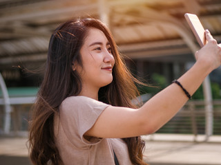 Smiling young asian woman making selfie photo on smartphone in the city.