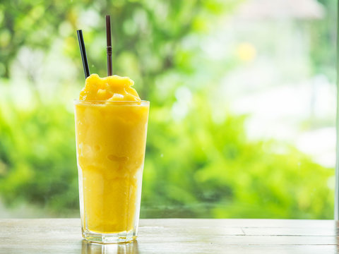 Mango smootie with green background on wood table