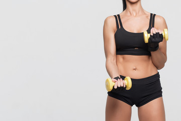 Fitness woman with barbells on grey background