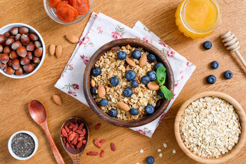 Healthy lifestyle breakfast with granola, honey, oats, superfoods and chia seeds. Dieting, healthy eating, weight loss concept. Table top view