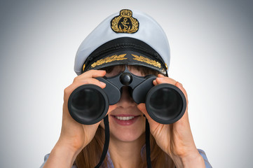 Happy female captain looks through a binoculars
