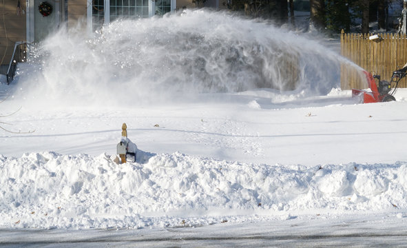 man operating snow blower to remove snow on driveway