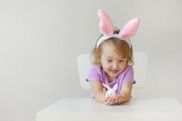 Happy Easter. The lovely girl with ears of a rabbit holds in hand a small egg