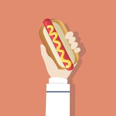 Hand holding hot dog raised up