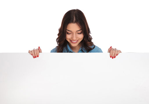 smiling casual woman standing above a big blank board