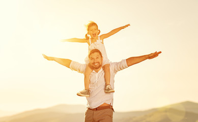 father's day. child daughter sits on her dad shoulders outdoors on a summer