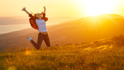 Happy woman jumping and enjoying life  at sunset in mountains