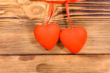 Two red hearts on a wooden background. Top view