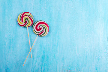 Two round lollipops with many colors in a spiral on turquoise copy space background