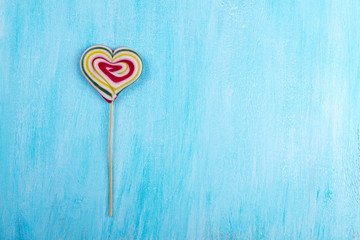 Striped colorful  heart shaped lollipop for Valentine's Day with turquoise copy space background.