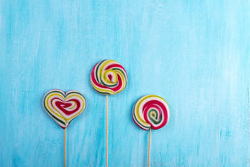 Cute colorful round lolipop and lollipop looks like a heart on turquoise copy space background