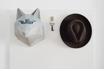 Coat rack with paper wolf head, vintage key and hat.
