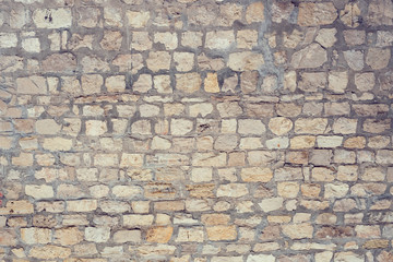 Part of a uneven stone wall with cement Background, texture