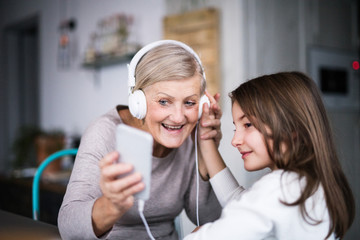 A small girl and grandmother with smartphone at home.
