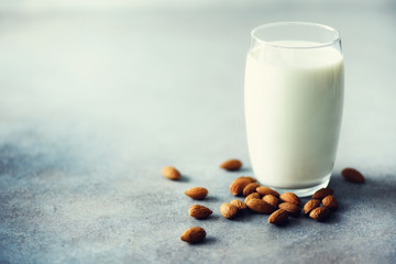 Almond milk in glass with almonds nuts on grey concrete background, copy space. Vegan alternative food, clean eating concept