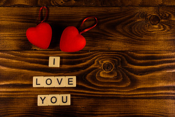 "Two red hearts on a wooden table. ""I love you"" inscription. Top view"