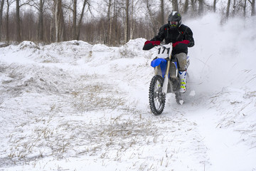 Sportsman racer man fulfills a fast ride on a motorcycle on the road extreme. The race track is very uneven. Cloudy winter day with a snowstorm.